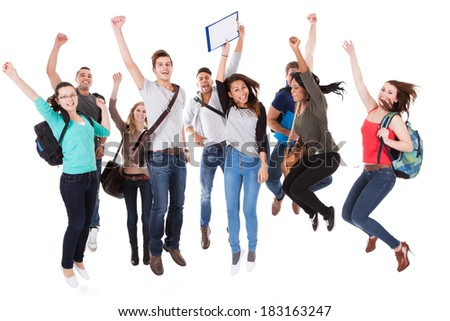 Full length portrait of successful university students with arms raised jumping over white background