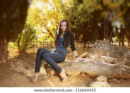 Full length portrait of teen young woman sitting, outdoors