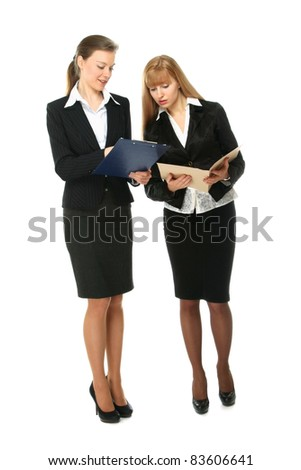 Full length portrait of two young attractive business women discussing something , isolated on white background