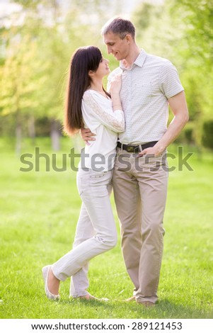 Full length portrait of young man and woman on date in park, talking to each other, girlfriend leaning on her boyfriend