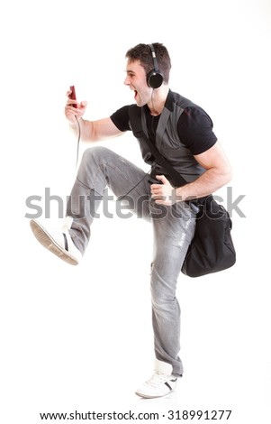 Full length portrait school boy phone isolated on white running while listening to music