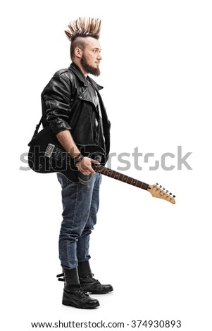 Full length profile shot of a young punk rocker holding an electric guitar isolated on white background