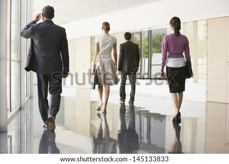 Full length rear view of business people walking on marble flooring in office