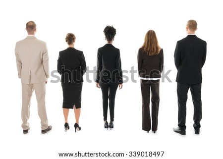 Full length rear view of business team standing against white background