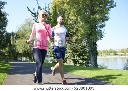Full length shot of a sporty woman and man running together outdoor.