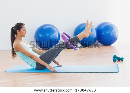 Full length side view of a sporty young woman with exercising ring in fitness studio