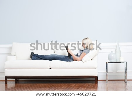 Full length view of woman reclining on white couch and reading a book. Horizontal format.