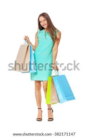 Fullbody portrait of beautiful happy woman with bags isolated on white. Shopping concept.