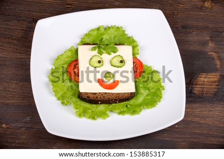 Fun food for kids - face on bread, made from cheese, lettuce, tomato, cucumber and pepper.