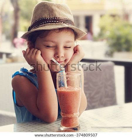 Fun kid girl in hat screwing up her eyes and waiting the moment to drink the smoothie tasty juice on summer background in cafe. Toned closeup portrait