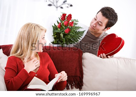 Fun Valentine's Day Holiday series with young Caucasian couple sitting around exchanging gifts.