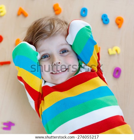 Funny child playing with lots of colorful plastic digits or numbers, indoor. Kid boy wearing colorful shirt and having fun with learning math