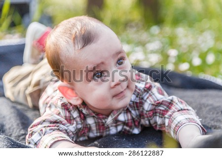 Funny face of cute 6 months old baby with Light brown hair in red checkered shirt and beige pants: he's biting his lips and puffing cheeks