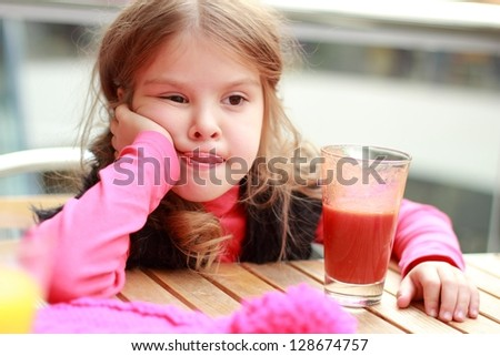 Funny girl at cafe indoor/Cute baby drinks tomato juice in cafe