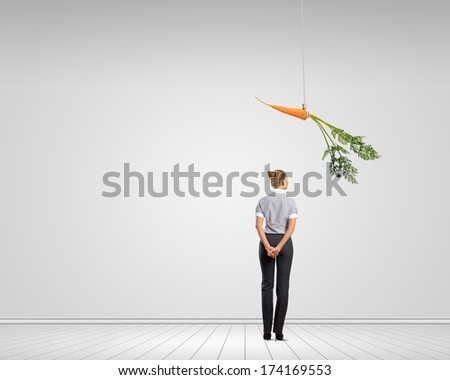 Funny image of businesswoman chased with carrot - stock photo
