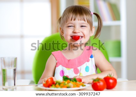 funny kid girl eating healthy food vegetables at home