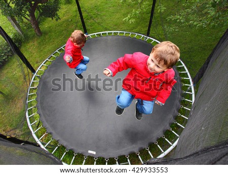 Funny kid playing and jumping on a outdoor trampoline. Children enjoying life. Vacations on countryside. Healthy lifestyle. Multi exposure of only one child playing on garden.