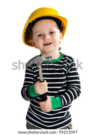 Funny little boy in yellow helmet playing with hammer