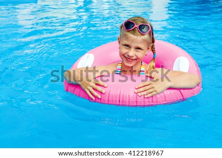 Funny little girl swims in a pool in a pink life preserver