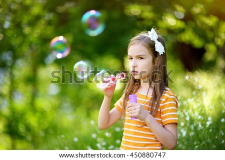 Funny lovely little girl blowing soap bubbles on a sunset outdoors on beautiful summer day