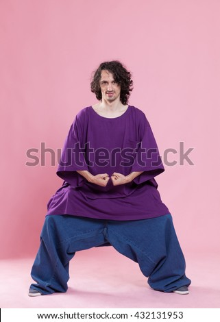 Funny portrait of a young man wearing a very large jeans and shirt. Conceptual image with weight loss themes.