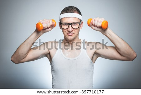 Funny weak man tries to lift a weight - dumbbells his biceps - muscle, isoalted on gray white.