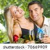 Funny young happy couple with gift and rosa, outdoors - stock photo