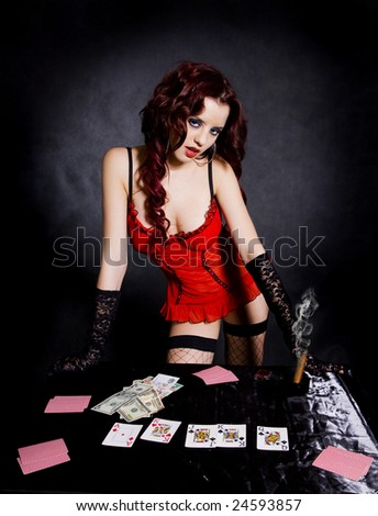 gambling pretty woman in beautiful lingerie. Over black background