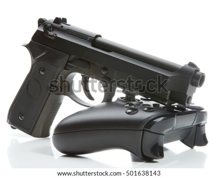 Game controller and a real handgun near it - close up studio shot. Virtual and real life concept