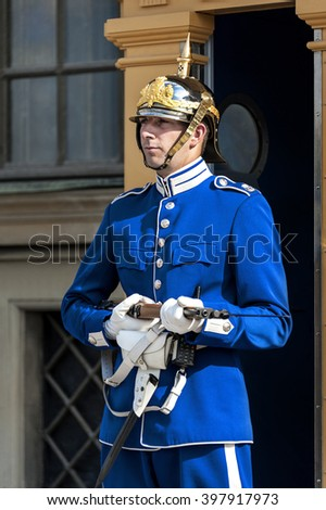 Gamla Stan; Stockholm; Sweden - August 08; 2014: One guard of the traditional Livgarde in blue uniform with yellow guard house and part of King's Castle (Kungliga slottet) in the background