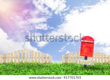 garden with a red postbox and wooden picket fence