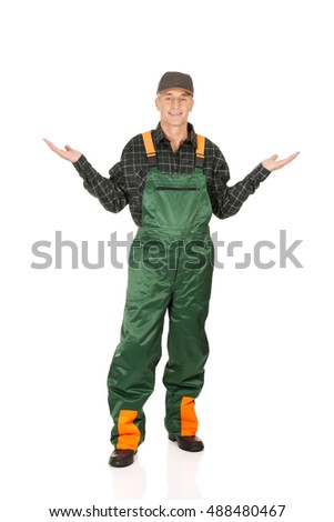 Gardener in uniform showing space with both hands