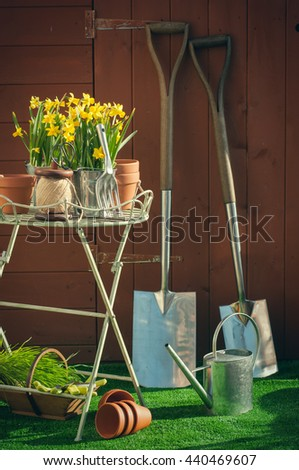 Gardening concept with utensils in front of garden shed - vintage feel