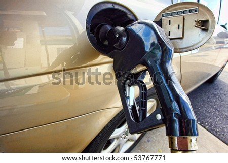 Gas station pump nozzle inserted into a car fuel tank intake to fill up the vehicle with premium unleaded gasoline