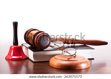 Gavel, a book of laws and glasses, a bell on the table walnut