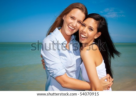 Gay couple standing at the beach, looking into camera