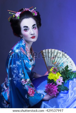 Geisha. Young woman in blue kimono with fan and with flowers in her hair.