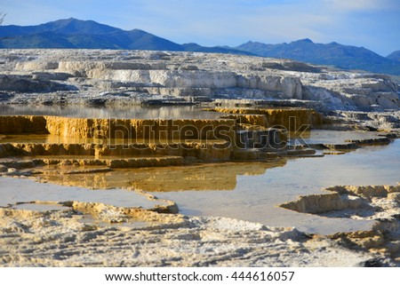 Geothermal flow of hot, carbonate rich water, forms cascading, dark orange travertine terraces, with steam rising and mountains in the background, at Mammoth Hot Springs in Yellowstone, Wyoming