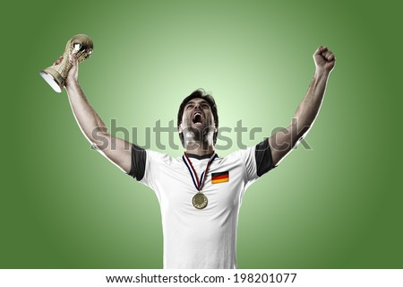 German soccer player, celebrating the championship with a trophy in his hand. On a green background.