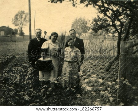 GERMANY, ROSTOCK - CIRCA 1930s: An antique photo of two men, two women and a little boy with accordion posing in the garden behind the fence of the grid-netting