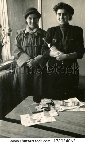 GERMANY -  1960s: An antique photo shows Two women posing with a bottle of wine in front of a table on which lay documents and a little US dollars