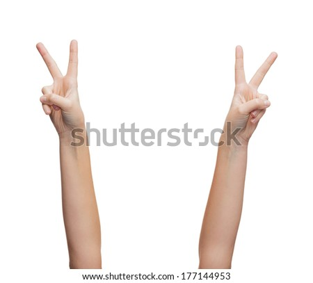 gesture and body parts concept - woman hands showing v-sign