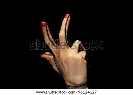 Gesturing female hand in black gloves over black background