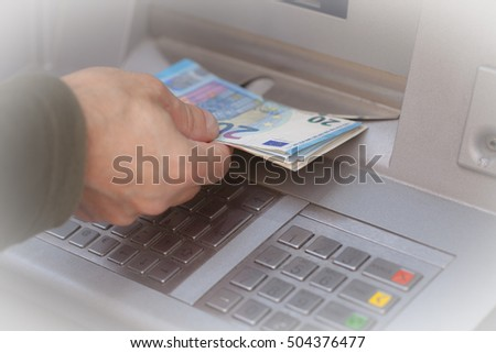 Getting banknotes at ATM machine, background with an intentional blur effect applied.