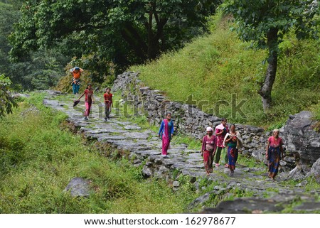 GHANDRUK - OCT 6: A group of Gurung women in traditional Nepalese clothes going to work in the mountains. Gurungs are the biggest ethnic group in the Himalayas. On Oct 6, 2013 in Ghandruk, Nepal