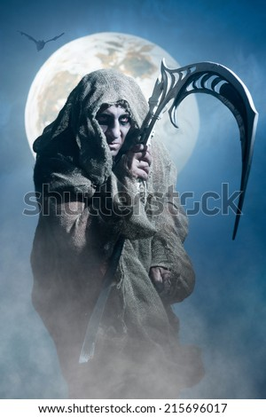 Ghost in rags with scythe on the background of the moon