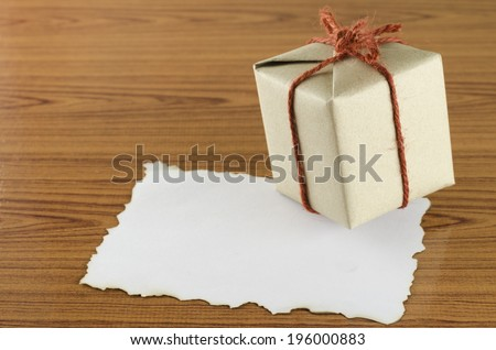gift box with paper write your note on wood background