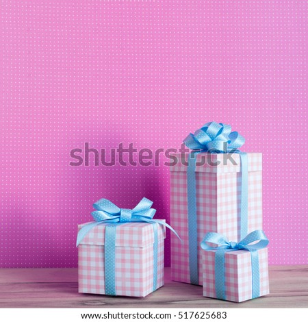 Gifts in a beautiful and elegant package on the wooden table. Pink background