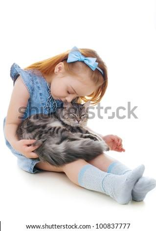 Ginger girl sits on the floor holding a cat on her knees