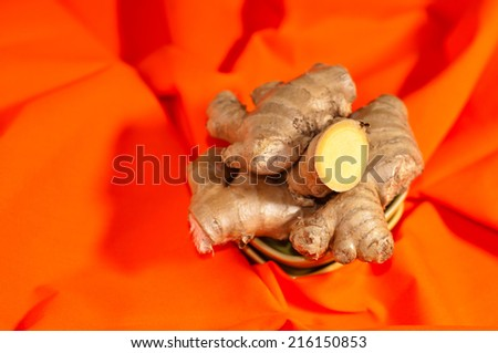 ginger slices of whole roots on an orange background